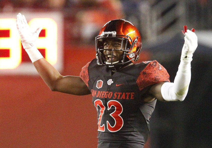 The Aztecs' Damontae Kazee holds up his arms after penalty call against the Aztecs during the second quarter of the Aztecs game against Air Force at Qualcomm Stadium in San Diego on Saturday.