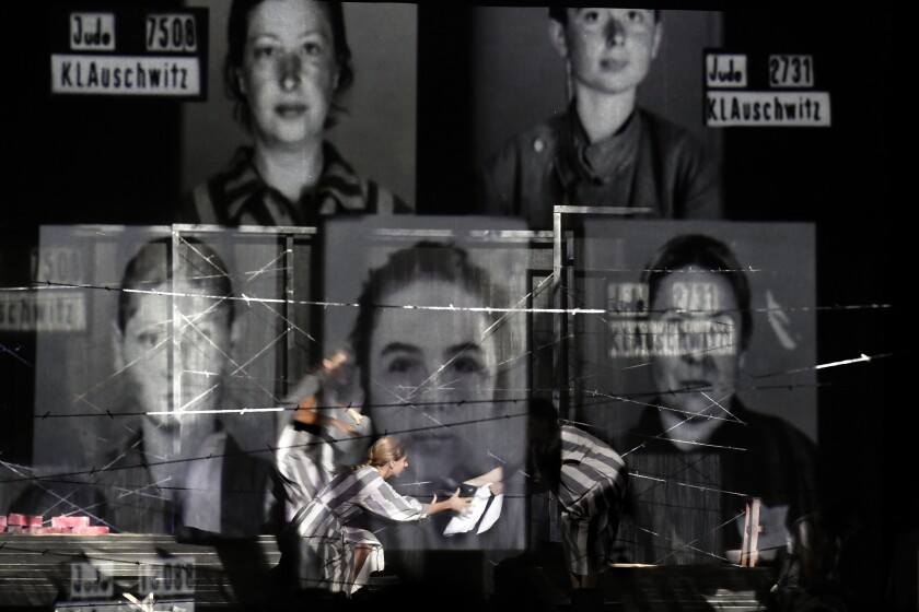"Portraits of Auschwitz death camp prisoners are displayed on a mesh as actresses of the Jewish State Theatre, perform during the premiere of the ""The Beautiful Days of My Youth"" play, based on the diary of Romanian Jewish Holocaust survivor Ana Novac, in Bucharest, Friday, Oct. 16, 2020. Maia Morgenstern, head of the Jewish State Theater and a Romanian Jewish actress best known for playing Mary in Mel Gibson's controversial 2004 movie ""The Passion of the Christ,"" described the play's staging in an interview with The Associated Press as an ""all-feminine project."" (AP Photo/Andreea Alexandru)"