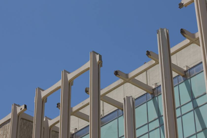 The top edge of LACMA's columned façade — with pieces missing — is seen against a blue sky