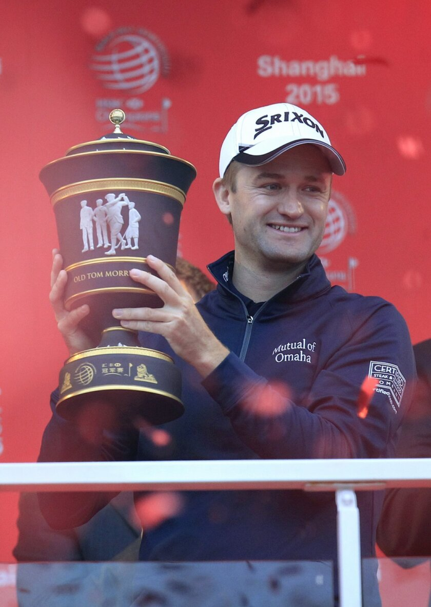 Russell Knox of Scotland holds his champion trophy during the award ceremony of  the HSBC Champions golf tournament at the Sheshan International Golf Club in Shanghai, China Sunday, Nov. 8, 2015. (AP Photo)