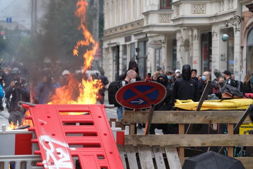 """FILE - In this Sept. 18, 2021 file photo, masked participants stand behind a barricade in Leipzig, Germany. After the official end of the """"We are all LinX"""" demonstration, barricades were erected and set on fire in the Connewitz district of Leipzig. The German Journalists Association on Monday condemned attacks by police against reporters covering a far-left protest in the eastern city of Leipzig on Saturday. (Sebastian Willnow/dpa via AP)"""