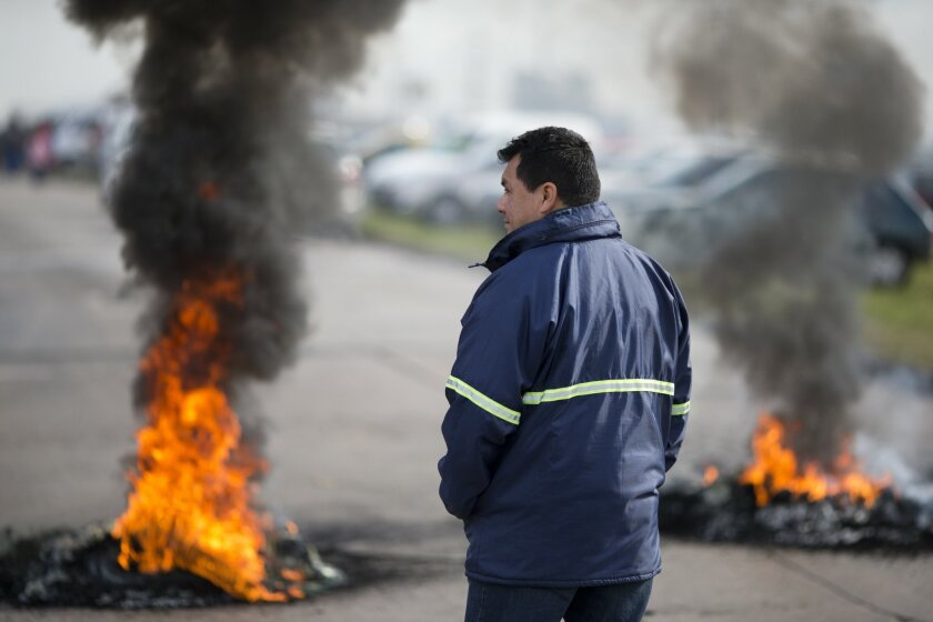 "A worker stands next to burning tires outside the entrance of RR Donnelley printing plant in the outskirts of Buenos Aires, Argentina, Monday, Aug. 11, 2014. RR Donnelley, a Fortune 500 company from Chicago, closed its plant in Argentina without warning catching its 400 workers by surprise when they showed up for work Monday morning. The company posted a letter outside it's entrance announcing its closing due to ""unsolvable crisis."" (AP Photo/Victor R. Caivano)"