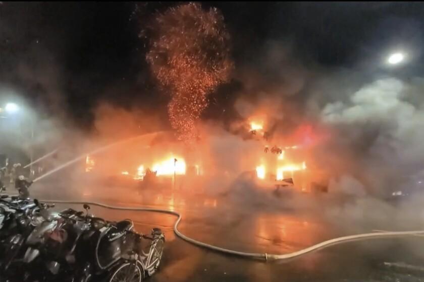 En esta imagen tomada de un video de la cadena taiwanesa EBC, bomberos combaten las llamas en un edificio de Kaohsiung, en el sur de Taiwán, el jueves 14 de octubre de 2021. (EBC via AP )