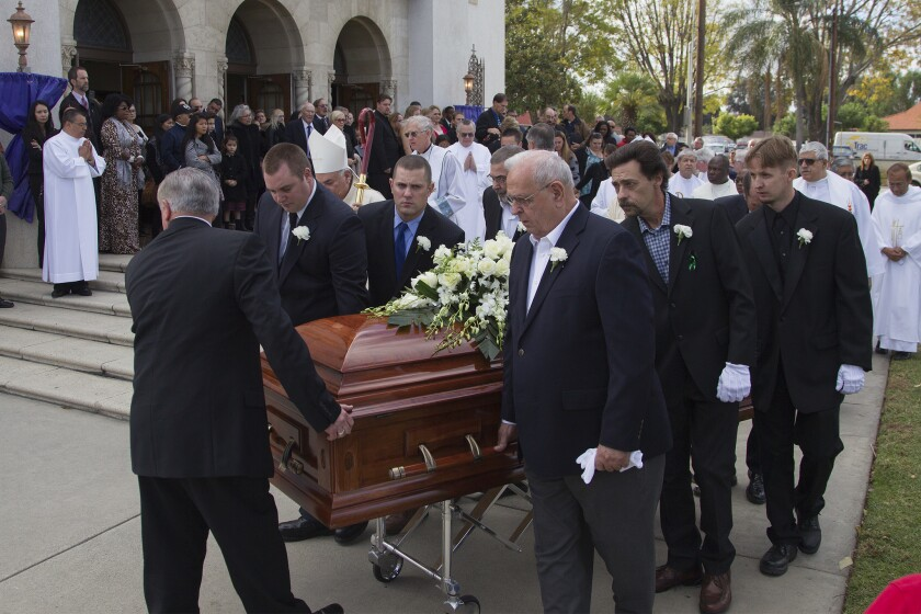 Pallbearers carry the casket of Damian Meins to an awaiting hearse after funeral services at St. Catherine of Alexandria.
