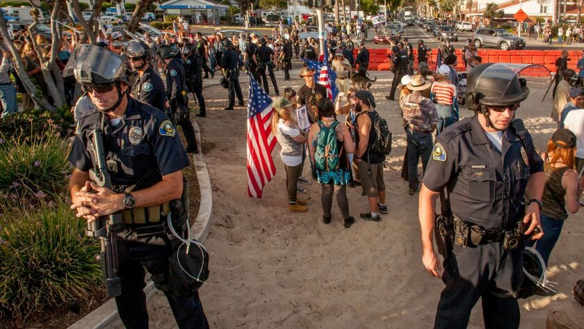 Anaheim police stand watch during last month's America First! demonstration at Laguna's Main Beach. The Laguna Beach City Council on Tuesday adopted an ordinance that bans people from bringing certain items to similar events.