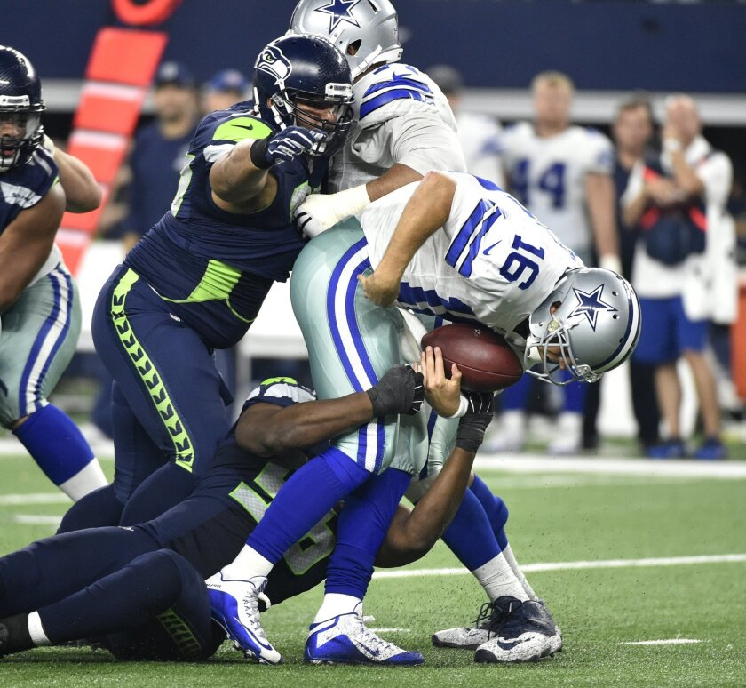 Seattle Seahawks' Cliff Avril, bottom, and Jordan Hill, left, combine to sack Dallas Cowboys' Matt Cassel (16) in the second half of an NFL football game Sunday, Nov. 1, 2015, in Arlington, Texas. The Seahawks won 13-12.  (AP Photo/Michael Ainsworth)