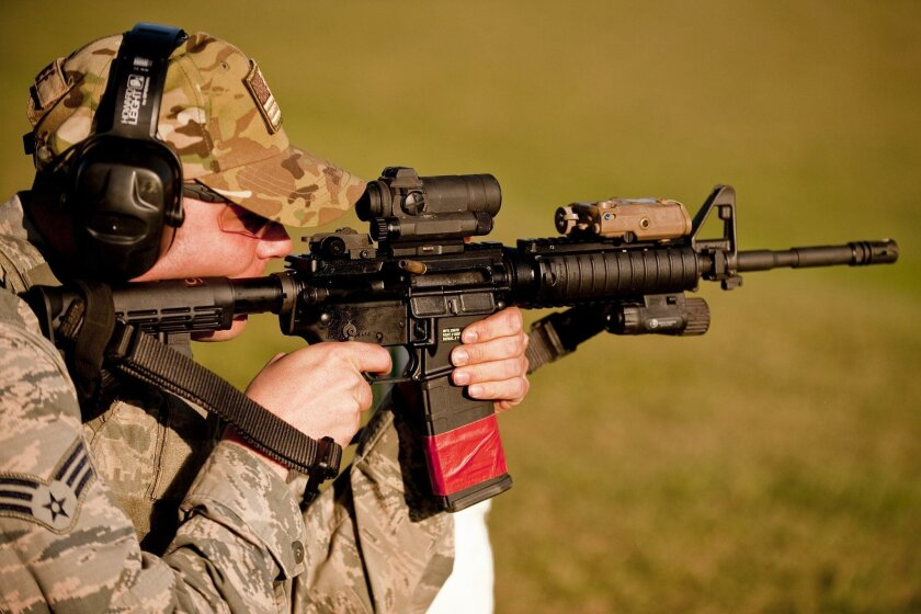 An Air National Guard senior airman fires his M4 carbine, with the Advanced Target Pointer/Illuminator LASER AN/PEQ-15 attached. It is the light-colored device mounted atop the barrel of the weapon.