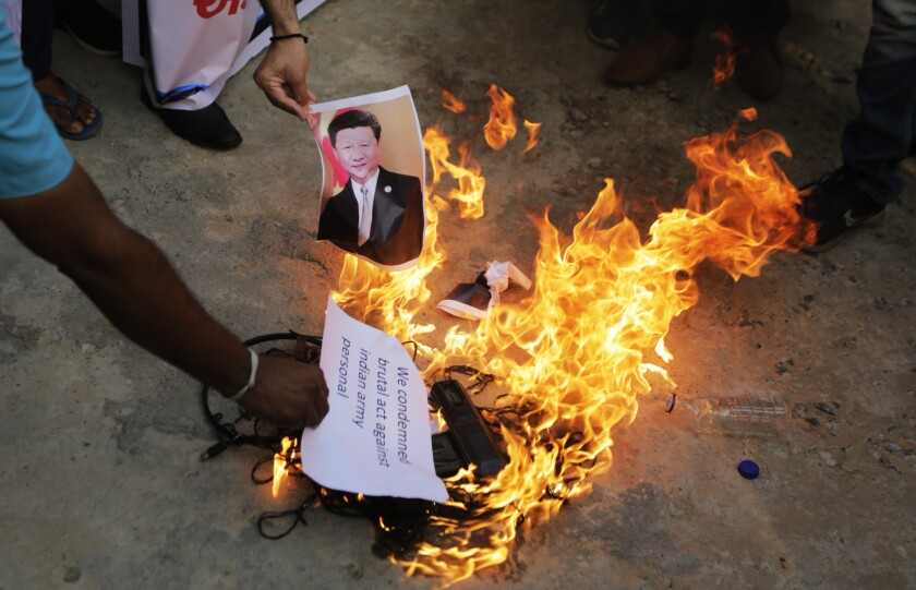 A man burns an image of Chinese President Xi Jinping during a protest in Ahmedabad, India, on June 16, 2020.