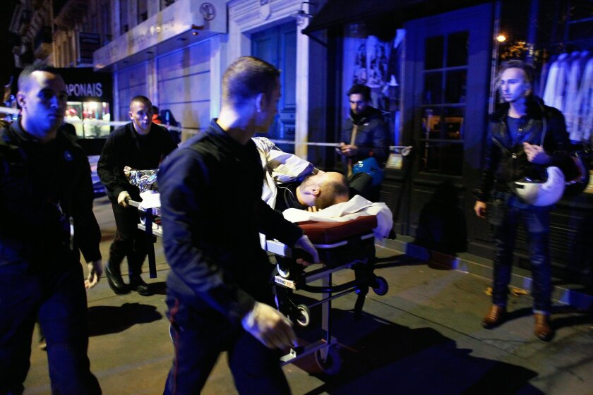 A person is being evacuated after a shooting, outside the Bataclan theater in Paris, Saturday, Nov. 14, 2015. A series of attacks targeting young concert-goers, soccer fans and Parisians enjoying a Friday night out at popular nightspots killed over 100 people in the deadliest violence to strike Fra