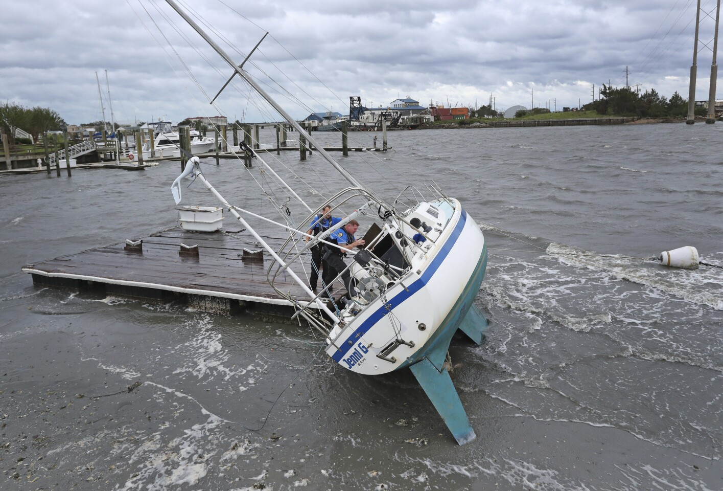 Beaufort Police Officer Curtis Resor, left, and Sgt. Micheal Stepehens check a sailboat for occupants in Beaufort, N.C. after Hurricane Dorian passed the North Carolina coast on Friday, Sept. 6, 2019. Dorian howled over North Carolina's Outer Banks on Friday — a much weaker but still dangerous version of the storm that wreaked havoc in the Bahamas — flooding homes in the low-lying ribbon of islands and throwing a scare into year-round residents who tried to tough it out. (AP Photo/Tom Copeland)