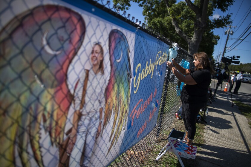 A woman places a decoration near a poster after attending the funeral service of Gabby Petito at Moloney's Funeral Home in Holbrook, N.Y. Sunday, Sept. 26, 2021. (AP Photo/Eduardo Munoz Alvarez)