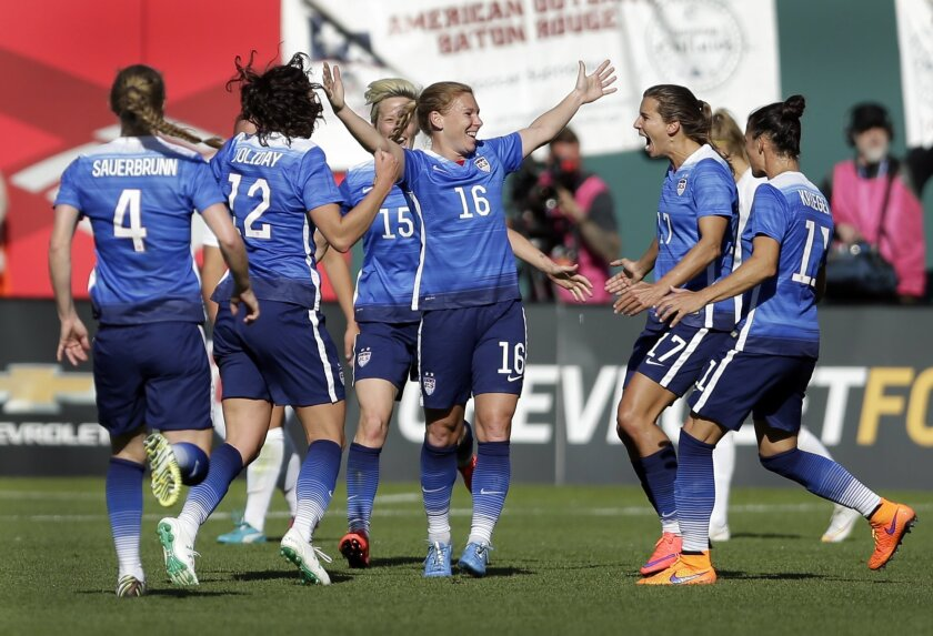 ADVANCE FOR WEEKEND EDITIONS, MAY 30-31 - FILE - In this April 4, 2015, file photo, United States' Lori Chalupny (16) is congratulated by teammates after scoring during the second half of an exhibition soccer match against New Zealand in St. Louis. Chalupny remembers the sinking feeling when she was told that she couldn't play for the U.S. national team because of concussions. With the World Cup looming, Chalupny contacted U.S. Soccer last summer with a comeback in mind. Accepted back onto the team, the next step was proving that she belonged. Now she's going to Canada. (AP Photo/Jeff Roberson, File)