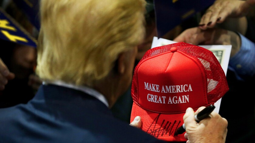 Donald Trump signs one of his iconic campaign hats during an event in Iowa in January.