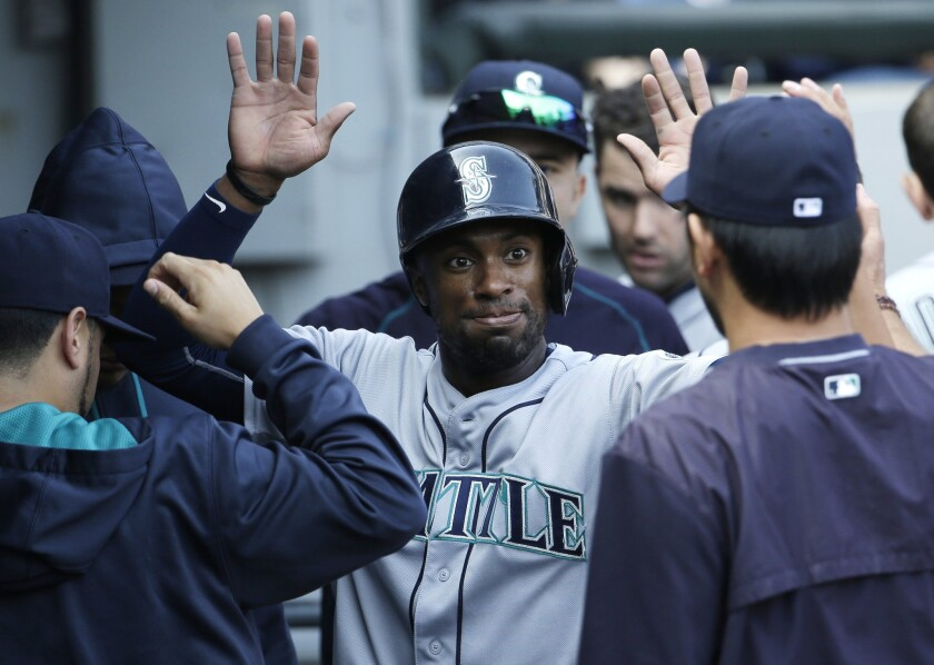 Mariners outfielder Austin Jackson celebrates with teammates after scoring on a single by Kyle Seager during a game against the White Sox on Aug. 30, 2015.