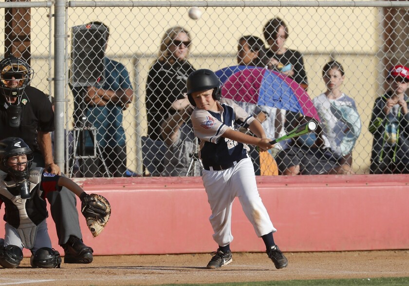 Costa Mesa National Little League's Donnie Bigelow singles in the tying run, 5-5, during the third i