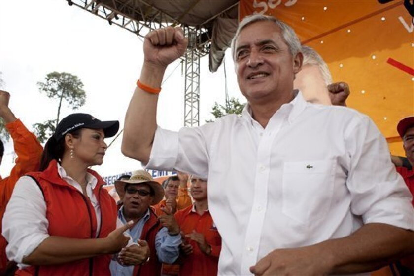 Patriot Party presidential candidate, Otto Perez Molina holds up his right fist during a campaign rally in the highlands of Chimaltenango, Guatemala, Saturday Sept. 3, 2011. The latest polls show the former general emerging as the frontrunner in the upcoming Sept. 11 elections. Running mate Roxana Baldetti is pictured on left. (AP Photo/Moises Castillo)