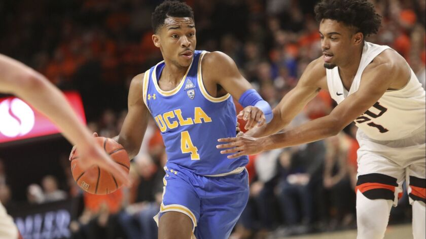 UCLA's Jaylen Hands dodges Oregon State's Stephen Thompson Jr. during the first half of an NCAA coll