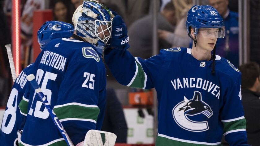Vancouver Canucks goalie Jacob Markstrom, left, is congratulated by teammate Elias Pettersson after defeating the Calgary Flames 4-3 on Saturday.