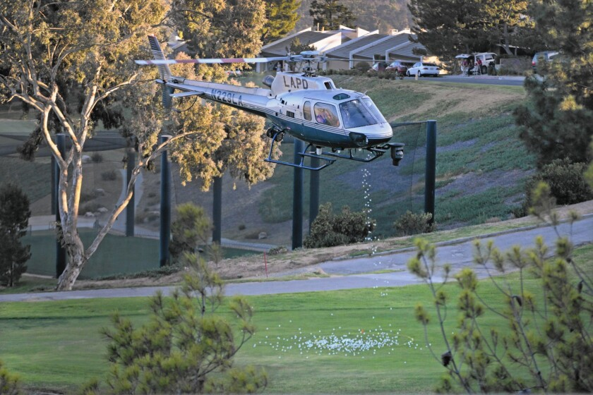 An LAPD helicopter drops golf balls over the course at the La Cañada Flintridge Country Club on Oct. 27.