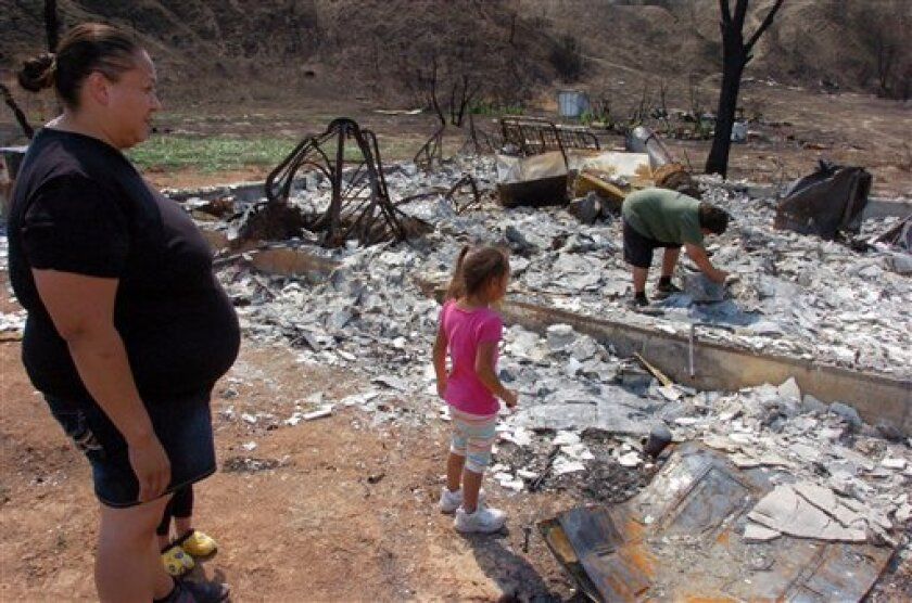 LuAnna Fox and three-year-old daughter Kamille watch her 10-year-old son Sheldon look for salvageable items from the ruins of the family's house on the Northern Cheyenne Indian Reservation in this Aug. 9 photograph. Wildfires have burned more than 90 square miles on the reservation since June. (AP Photo/Matthew Brown)