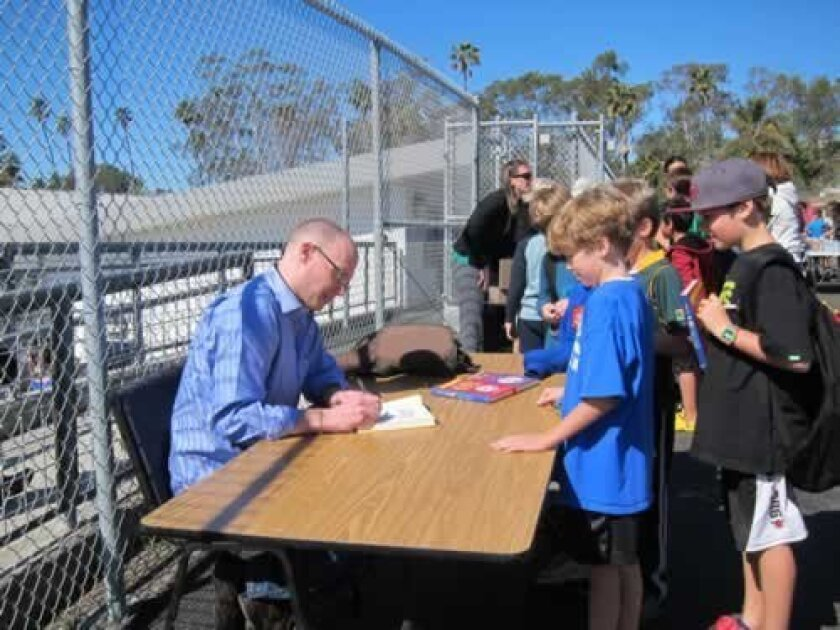 Peirce signs books for students after his presentation at Bird Rock Elementary School.