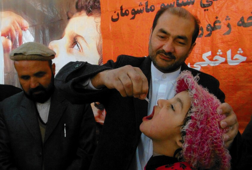 An Afghan health worker administers polio vaccine drops to a child during the first day of a vaccination campaign in Jalalabad, Afghanistan.