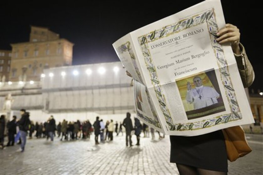 A reader looks at the first edition of the Vatican newspaper L'Osservatore Romano after the election of Pope Francis, the 266th pontiff of the Roman Catholic Church, in St. Peter's Square at the Vatican, Wednesday, March 13, 2013. Cardinal Jorge Bergoglio of Argentina was elected pope. (AP Photo/Al