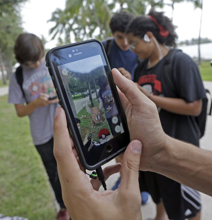"FILE - In this Tuesday, July 12, 2016, file photo, Pinsir, a Pokemon, is found by a group of Pokemon Go players at Bayfront Park in downtown Miami. The ""Pokemon Go"" craze has sent legions of players hiking around cities and battling with ""pocket monsters"" on their smartphones. (AP Photo/Alan Diaz,"