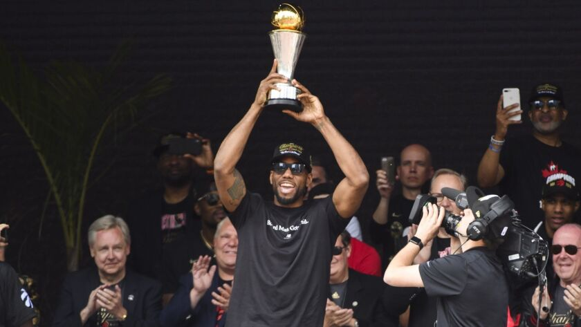 Toronto Raptors forward Kawhi Leonard hoists the MVP trophy next to teammates during the team's NBA