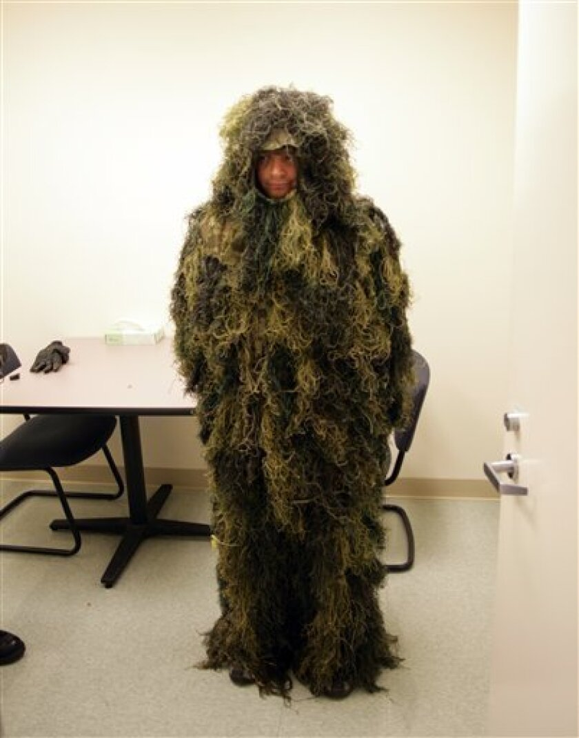"""FILE - This is a Thursday, Oct. 14, 2010 Washington County Sheriff's Office file handout photo of 36-year-old Gregory Liascos in a """"Ghillie"""" camouflage suit taken in Hillsboro, Ore. Authorities say Liasco, of Portland, Ore;, a burglary suspect dubbed Moss Man, failed to show up at his trial Tuesday, Oct. 11, 2011 in Hillsboro, Ore. and a warrant has been issued for his arrest. He is accused of breaking into the Rice Northwest Museum of Rocks and Minerals last October and hiding nearby in a camouflage suit that made him look like a mound of moss. (AP Photo/Washington County Sheriff's Office, File)"""
