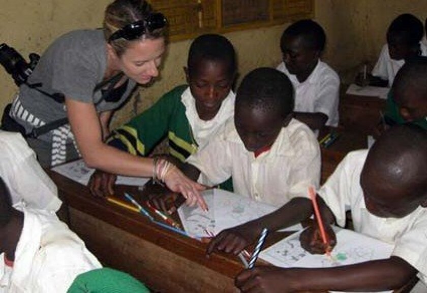 The Children's School educator Lisa Dutton assists students during her trip to Tanzania. Courtesy photo