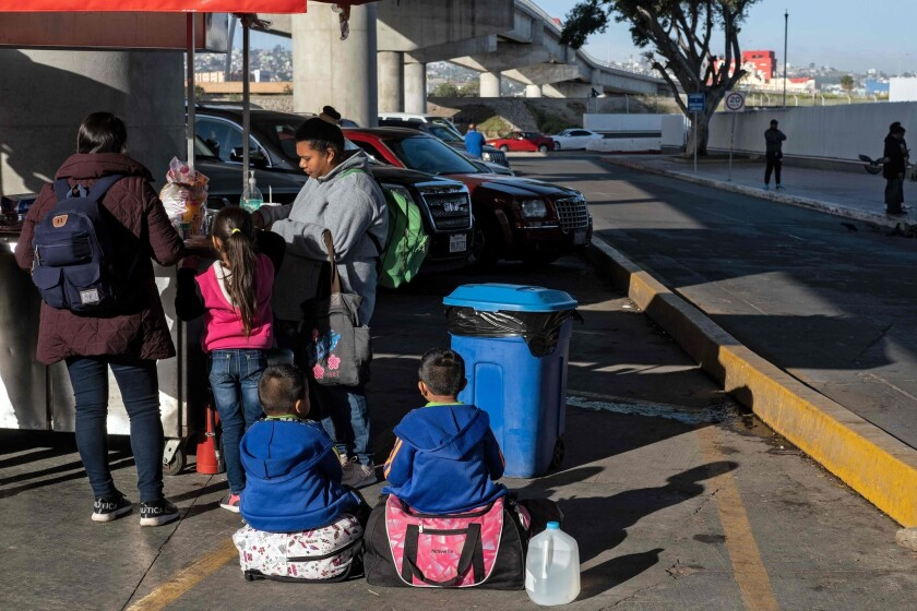 Asylum seekers eat outside the El Chaparral border crossing in Mexico.