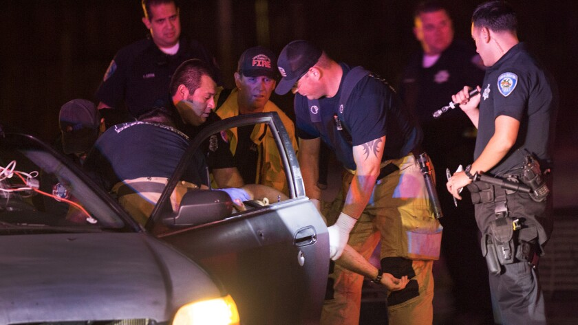 Firefighters and paramedics extricate Alejandro Herrera, 28, from his car after he was shot while sitting at an intersection on Aug. 10 in San Bernardino. Herrera died at the hospital.