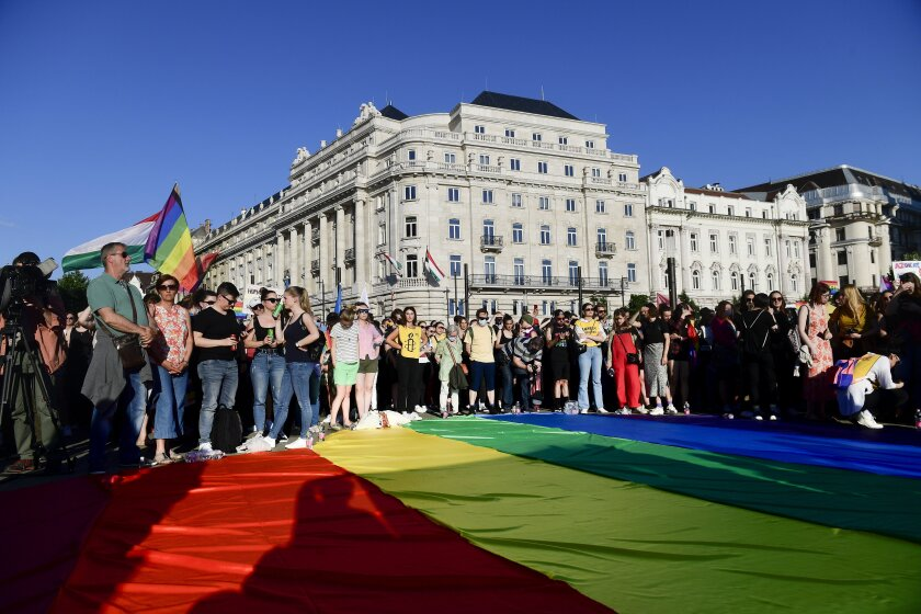 People unfurl a rainbow flag during an LGBT rights demonstration in front of the Hungarian Parliament building in Budapest