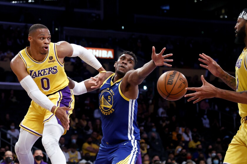 Los Angeles Lakers guard Russell Westbrook, left, passes the ball to forward Anthony Davis, right, while defended by Golden State Warriors center Kevon Looney during the first half of a preseason NBA basketball game in Los Angeles, Tuesday, Oct. 12, 2021. (AP Photo/Ringo H.W. Chiu)