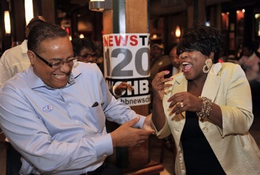 Detroit mayoral candidate Benny Napoleon, left, jokes with talk radio host Mildred Gaddis at Fishbones restaurant, his first campaign stop after casting his ballot Tuesday morning in the primary election, in Detroit, Mich., on Aug. 6, 2013. The top two vote getters of the 14 candidates for mayor will be on the ballot in November's general election. (AP Photo/Detroit News, John T. Greilick) DETROIT FREE PRESS OUT; HUFFINGTON POST OUT