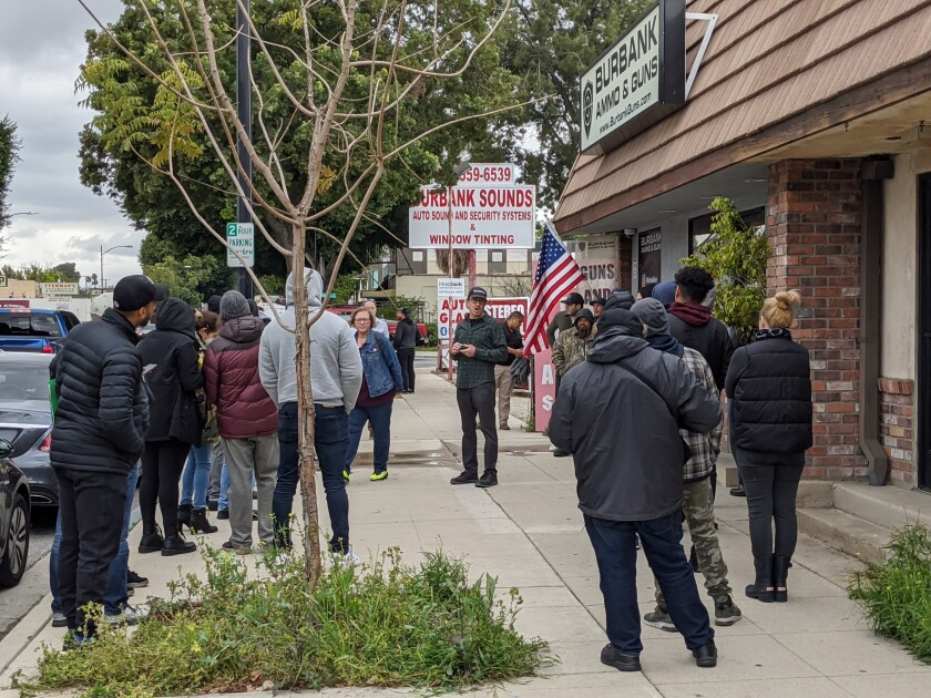 An employee of Burbank Ammo & Guns in Burbank talks to customers who were looking to purchase a firearm and ammunition in light of the coronavirus pandemic on Monday, March 16, 2020.
