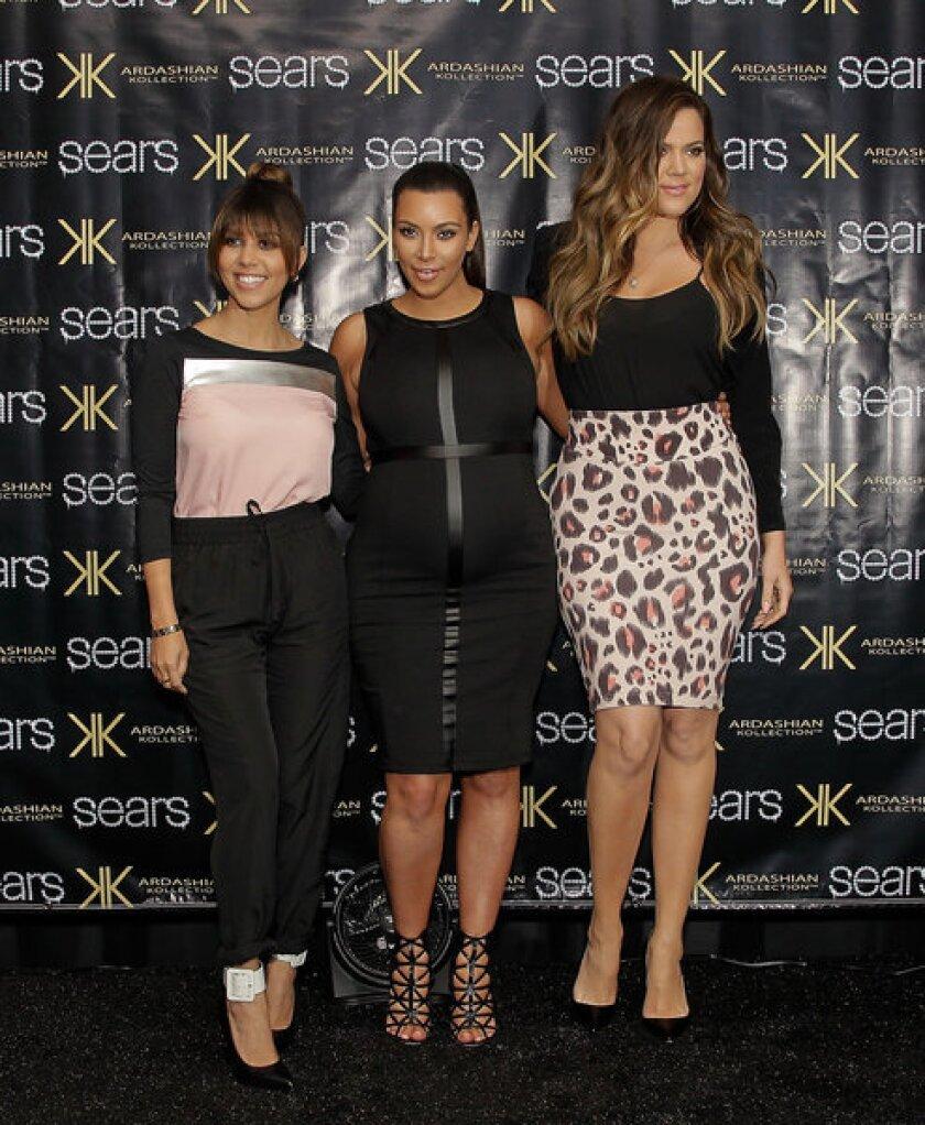 Kourtney Kardashian, left, Kim Kardashian and Khloe Kardashian Odom greet fans at a Sears in Houston.