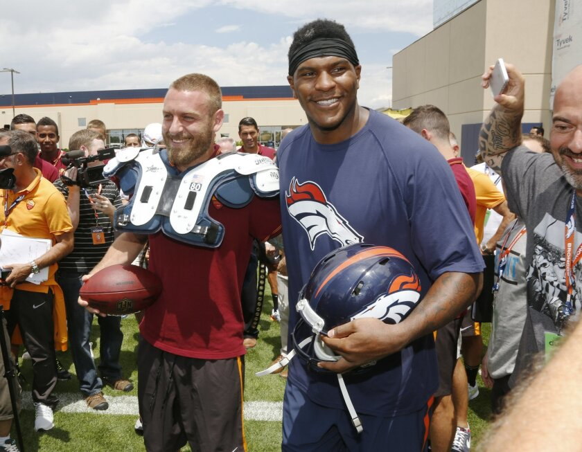 AS Roma player Daniele De Rossi, left, tries on the shoulder pads of Denver Broncos tight end Julius Thomas as members of the Italian soccer team meet Broncos players after the Broncos' NFL football training camp session in Englewood, Colo., on Friday, July 25, 2014. AS Roma is in Denver to face Ma