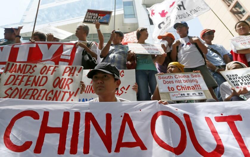 Manifestantes muestran carteles y pancartas durante una manifestación en el exterior del consulado chino antes de conocer el fallo sobre una disputa territorial con Filipinas por el mar de China Meridional, en un tribunal de La Haya. (AP Foto/Bullit Marquez)
