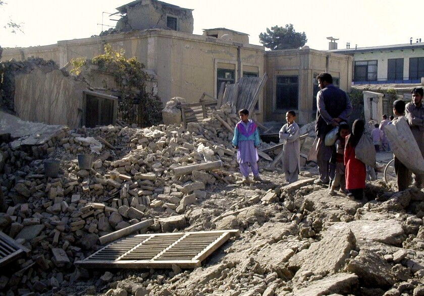 Afghans look at the debris of a destroyed house in Kabul on Oct. 17, 2001, after heavy U.S. led military strikes.