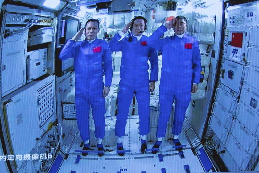 In this photo released by Xinhua News Agency, Chinese astronauts salute after successfully entering the Tianhe space station module as they are displayed on a big screen at the Beijing Aerospace Control Center in Beijing, on Thursday, June 17, 2021. China has launched the first three-man crew to its new space station in its the ambitious programs first crewed mission in five years (Jin Liwang/Xinhua via AP)