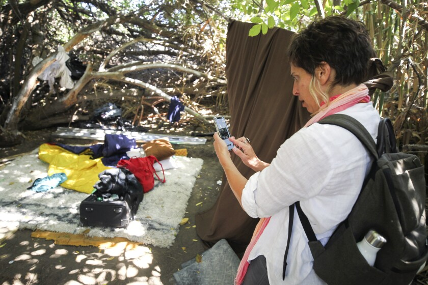 United Nations Special Rapporteur Leilani Farha uses her phone to take pictures of a homeless encampment as she and a group from the San Diego River Park Foundation take a tour of the San Diego River in Mission Valley on Tuesday, August 13, 2019.