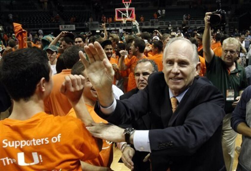 FILE - In this Nov. 28, 2012, file photo, Miami's head coach Jim Larranaga, right, is congratulated by fans after their 67-59 win over Michigan State in an NCAA college basketball game in Coral Gables, Fla. Larranaga, who led Miami to the Atlantic Coast Conference regular season and tournament titles and a No. 2 ranking, has been selected The Associated Press' coach of the year on Thursday, April 4, 2013. (AP Photo/Alan Diaz, File)
