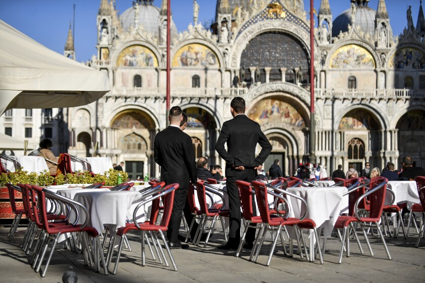 FILE - In this Friday, Feb. 28, 2020 file photo, two waiters wait for customers in a restaurant at St. Mark's Square in Venice, Italy. With the coronavirus emergency deepening in Europe, Italy, a focal point in the contagion, risks falling back into recession as foreign tourists are spooked from visiting its cultural treasures and the global market shrinks for prized artisanal products, from fashion to design. (Claudio Furlan/Lapresse via AP, File)