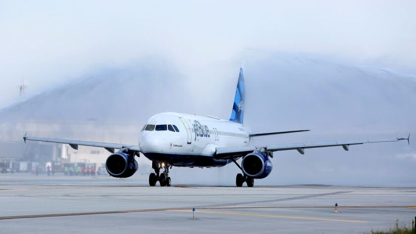 JetBlue's inaugural flight from Fort Lauderdale, Fla., to Mexico City taxis down the runway with a water salute. The New York-based airline plans to remove its fares and schedules from online travel booking sites.
