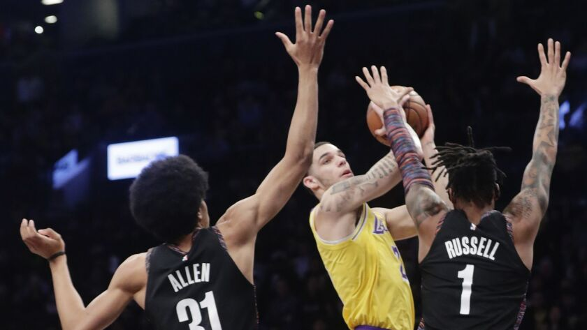 Los Angeles Lakers' Lonzo Ball looks to pass the ball away from Brooklyn Nets' D'Angelo Russell (1)