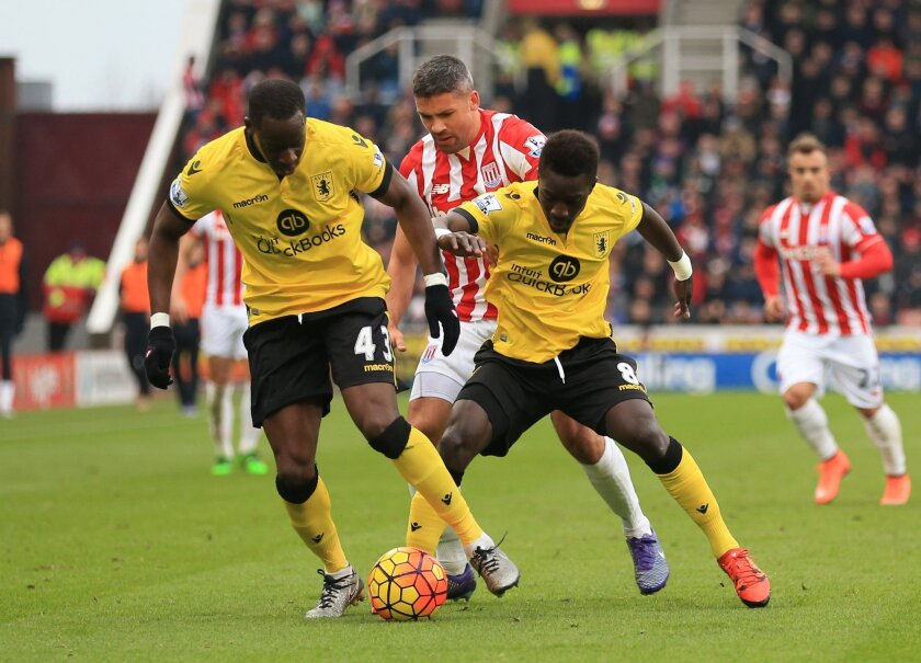 Stoke City's Jonathan Walters, center, battles for the ball with Aston Villa's Aly Cissokho, left, and Idrissa Gueye during the English Premier League soccer match between Stoke City and Astyon Villa at the Britannia Stadium in Stoke-on-Trent. Saturday Feb. 27, 2016. (Nigel French /PA via AP) UNITED KINGDOM OUT - NO SALES - NO ARCHIVES