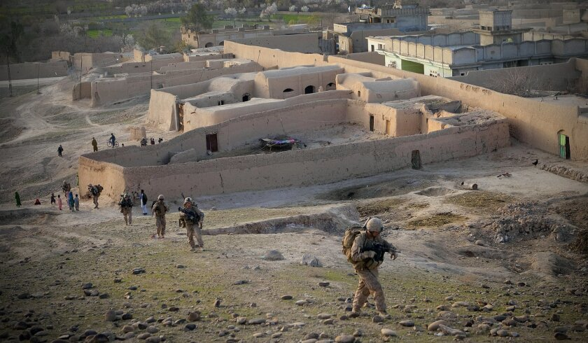 Marines from Lima Company move past a small village as they prepare to set up a position to monitor possible insurgent activity through the night.