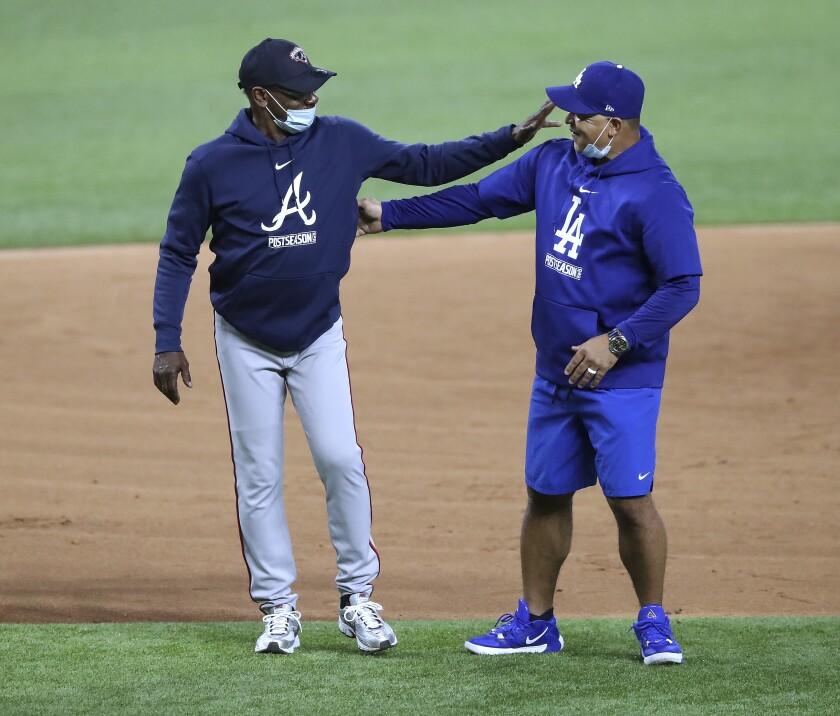 Atlanta Braves third base coach Ron Washington, left, and Los Angeles Dodgers manager Dave Roberts greet each other during team baseball workouts the day before facing in the best-of-seven National League Championship Series at Globe Life Field, Sunday, Oct. 11, 2020, in Arlington. (Curtis Compton/Atlanta Journal-Constitution via AP)